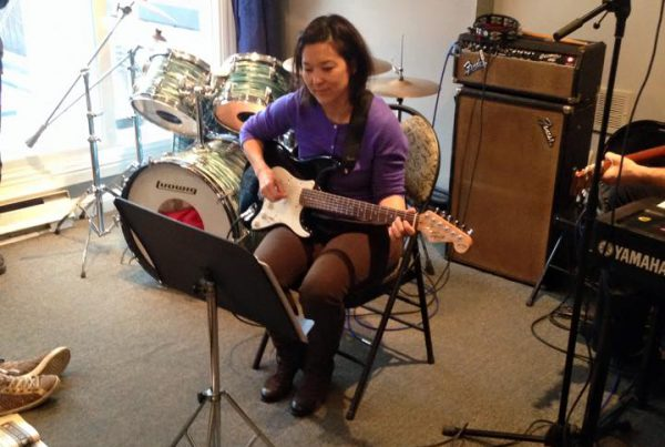 Woman playing guitar at Adult Student Recital